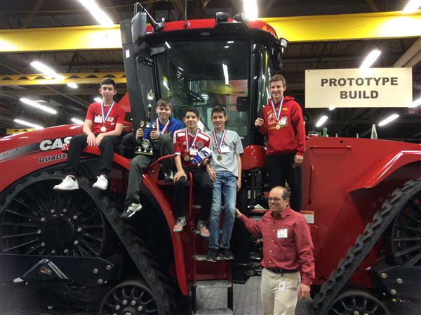 Students standing in front of a monster truck