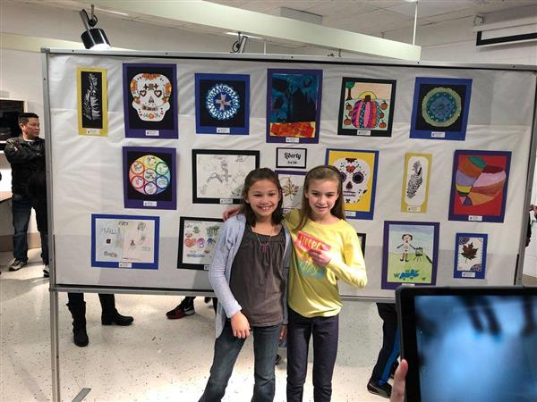 Two female students posing in front of their artwork