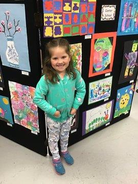 Student standing in front of her artwork