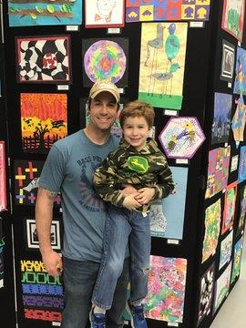 Student and parent standing in front of his artwork at the show
