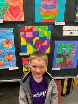 Student standing in front of his artwork at the show