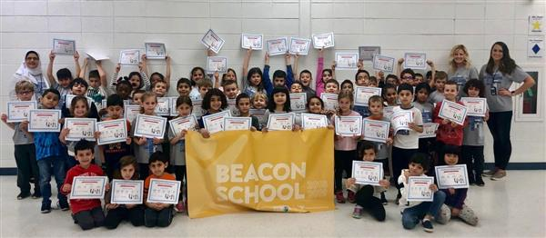 Students holding Beacon Award banner