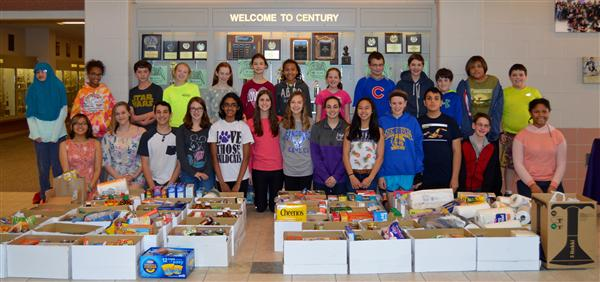 Junior high students standing behind boxes of donated food