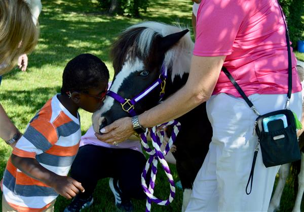 An early childhood student gives a therapy horse a kiss