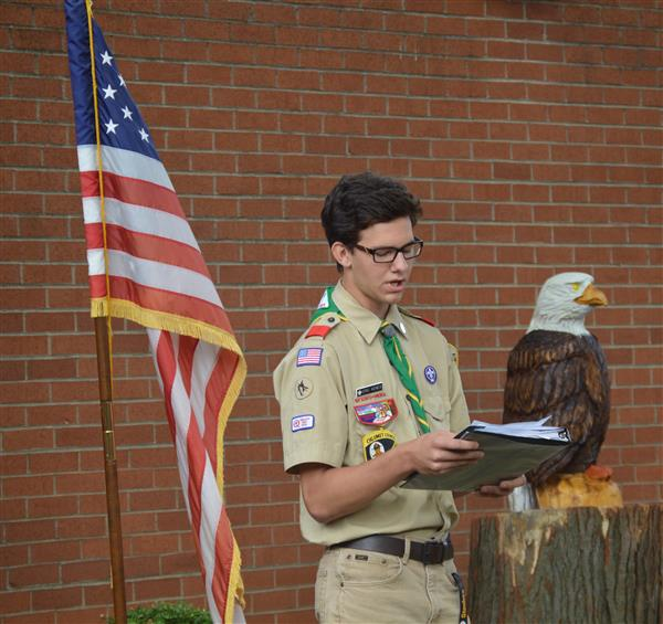 Eric Kenes in between the American flag and his statue and reading his speech
