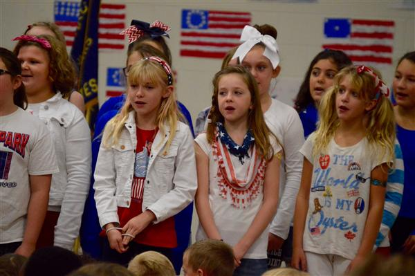 Elementary school students wearing red, white, and blue