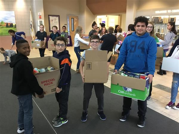 A group of students helping each other carry donations to the van