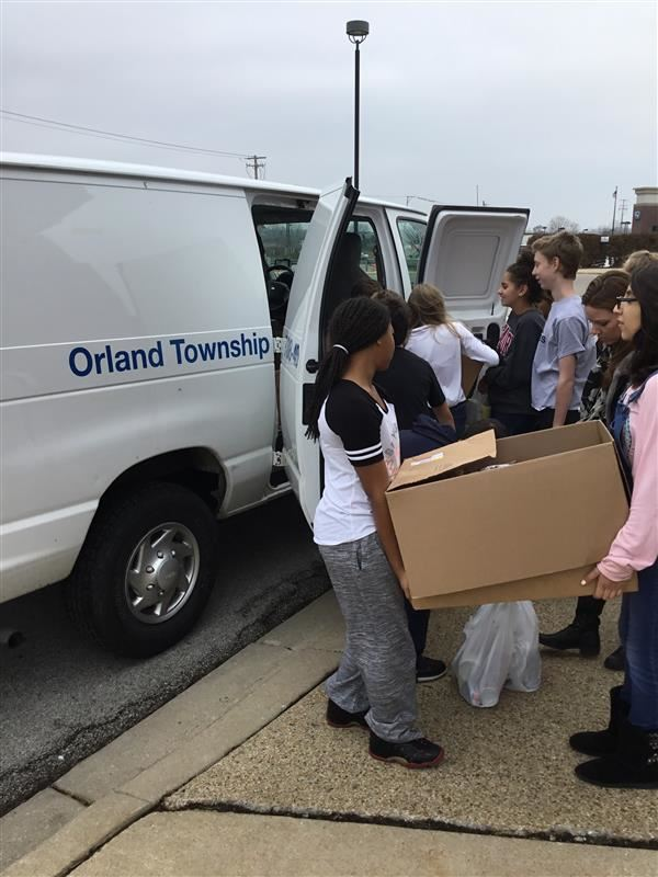 Students loading the boxes of donated items into the van