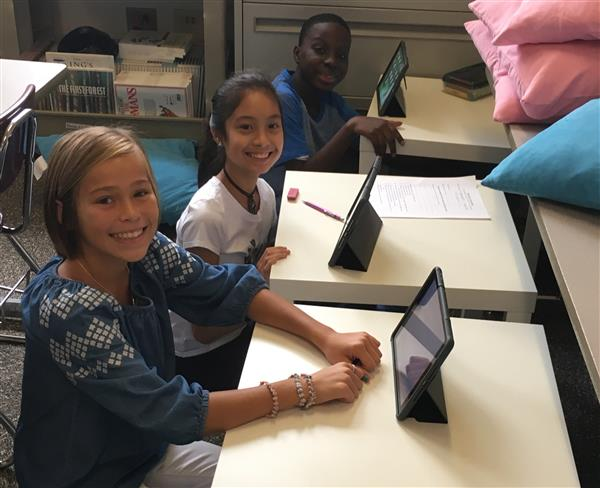 Three students working on their iPads in class