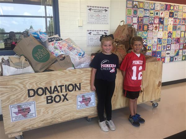 Students standing in front of a pile of donated items for the hurricane