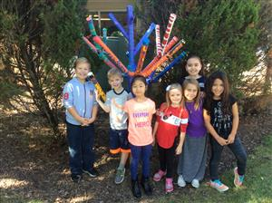Park School students standing in front of their tree sculpture