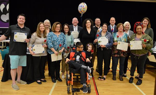 A group of educators standing with a student being recognized for an award